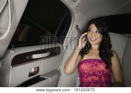 Asian woman talking on cell phone in limousine