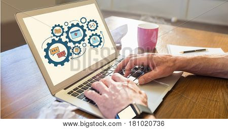 Digital composite of Businessman using laptop with gears displayed on screen