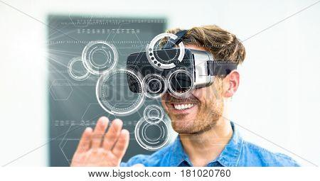 Digital composite of Digital composite image of smiling man using VR glasses