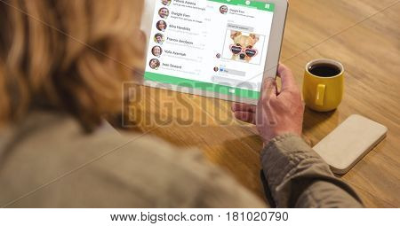 Digital composite of Rear view of man using digital tablet with social media interface on screen