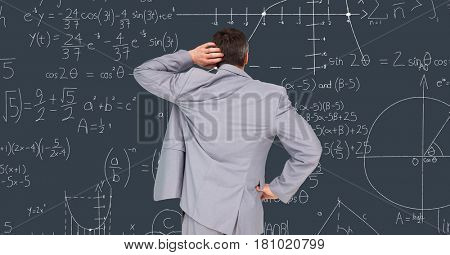 Digital composite of Confused businessman reading math equations