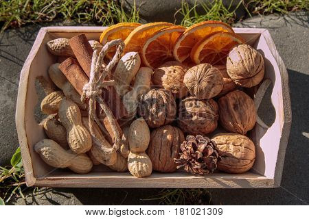 Little Wooden Box with Walnuts Groundnut Seeds Cinnamon Sticks and Dehydrated Orange Slices