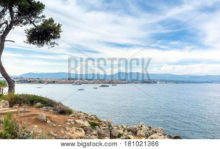 view over the bay with old town skyline and alpes maritimes from Cap d'Antibes Antibes