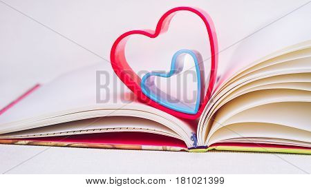 Red and blue hearts over diary book on white table. Front short, bright colours