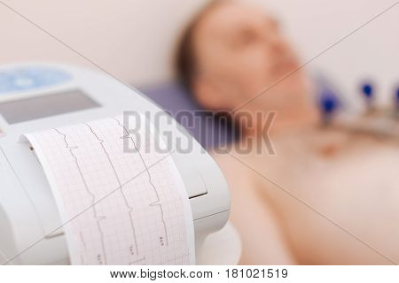 Writing of your heart. Calm patient mature man lying with some sensors being attached to his chest while special equipment shows his electrocardiographic tracings