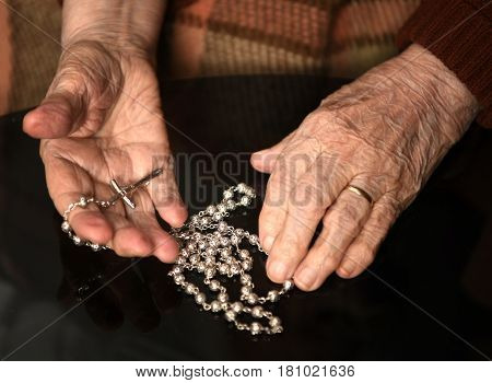 Close Up Of Old Woman Praying With Silver Rosary With Cross