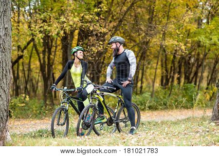 Cyclists With Bikes In Autumn Park