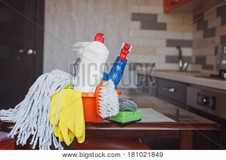 Cleaning set with products and supplies on kitchen table.