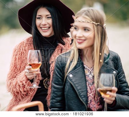 Happy young women sitting on sandy beach with glasses at alfresco picnic