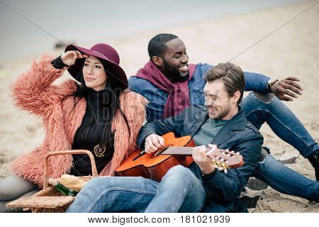 Happy smiling friends having fun and enjoying guitar while sitting on sandy beach at alfresco picnic