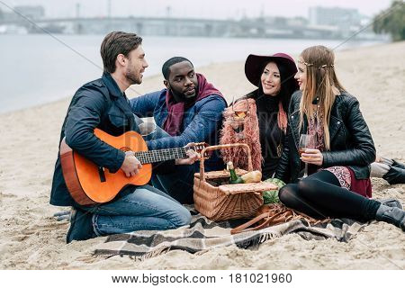 Happy Friends With Guitar At Alfresco Picnic