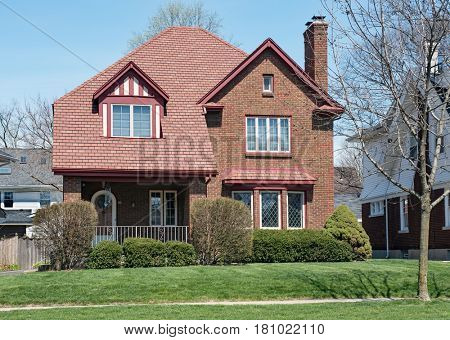 Brick House with Red Shingle Roof