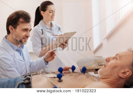 Providing support. Excellent competent cardiologist doing an electrocardiogram and dictating the results of it and the nurse writing them down