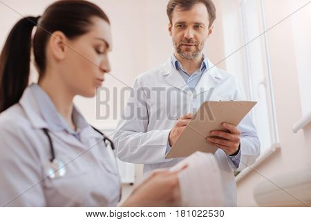 I value your opinion. Experienced unsure clever cardiologist asking his fellow doctor having a look at the cardiogram recording while figuring out the diagnosis