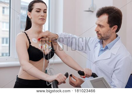 New ways of testing. Busy competent curious doctor using modern medical equipment and running some tests for diagnosing young woman