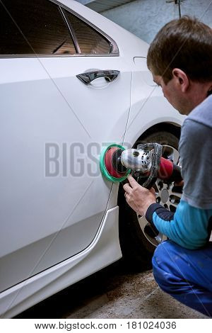 Polishing of the white car with the help of power tools on the service.