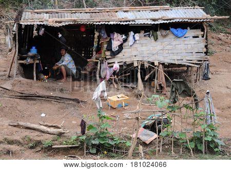 River Mekong, Laos - 7 January 2012: man cooking on his hut on river Mekong, Laos
