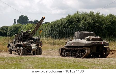WESTERNHANGER, UK - JULY 21: A broken down Sherman tank is recovered from the battlefield as a demonstration for the watching public at the War & Peace Revival show on July 21, 2016 in Westernhanger