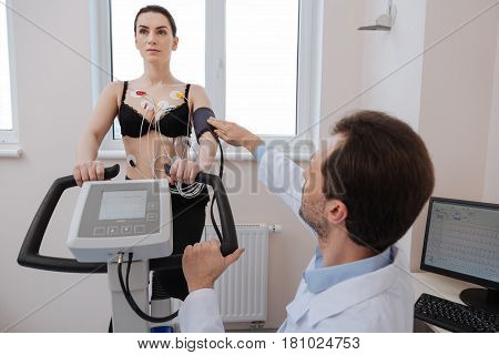Let me fix it for you. Ambitious distinguished precise doctor making sure the blood pressure gouge working right while his patient doing some exercises