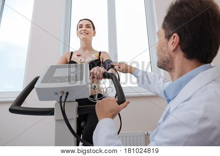 Having no problem with this. Active motivated gorgeous woman performing some stationary cycling while her doctor examining her performance for figuring out the diagnosis