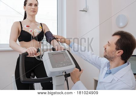 Just make it a little tighter. Lovely incredible competent cardiologist fixing the tonometer while a woman performing some exercises for indicating any possible heart pathologies