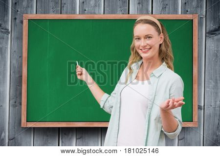 Digital composite of Portrait of happy female student standing against chalkboard