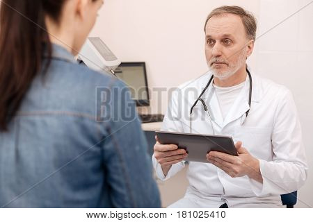 What are your symptoms. Successful private experienced doctor talking to his patient and listening her concerns while holding a tablet in his hands
