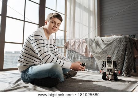 Time for games. Attractive boy with brown hair holding console in both hands crossing legs while sitting in semi position