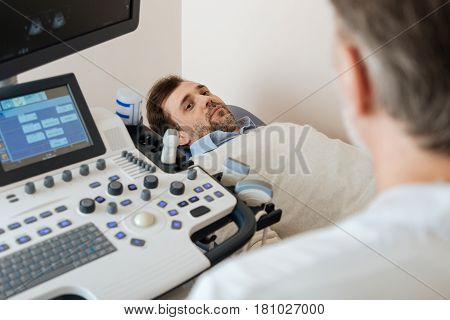 Paying a visit. Young attractive pleasant man lying on the medical bed and listening to the doctors instructions before staring the process