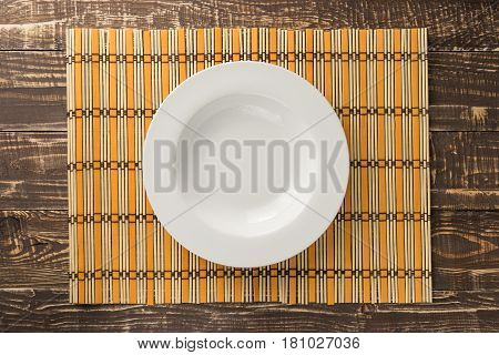 White empty dish on bamboo weave and wooden table background in top view