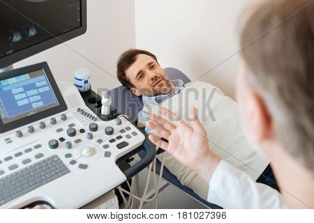 You should take care of yourself. Prominent mature local specialist explaining his patients something while he lying on medical bed and listening carefully