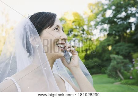 Asian bride talking on cell phone