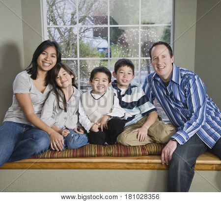 Mixed Race family in front of window