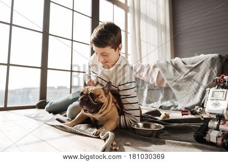 Playful mood. Smiling boy hugging his dog leaning on his elbow while expressing positivity