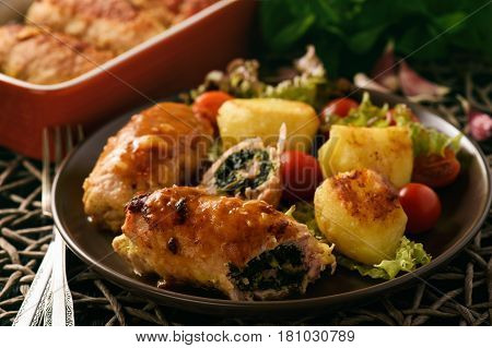 Spinach and cheese pork rolls (roulades) served with vegetables.