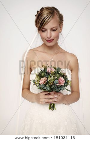 Daydreaming beautiful bride in studio holding flowers