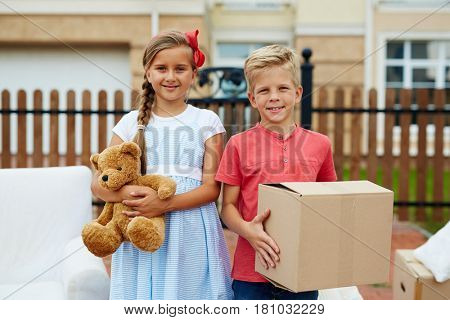 Little boy with box and his sister with teddybear looking at camera during relocation