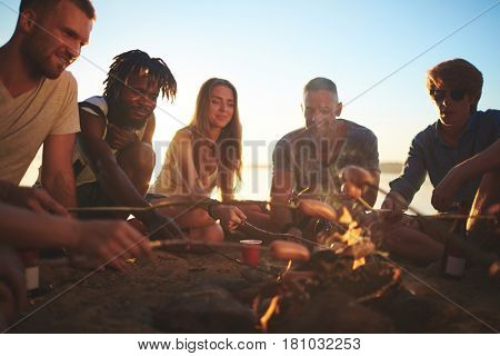 Young buddies roasting sausages on campfire by seaside