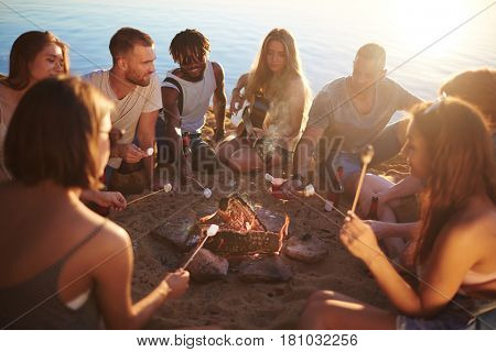 Group of restful friends roasting marshmallows while sitting by bonfire