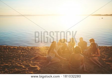 Several teenagers gathered around campfire by seaside