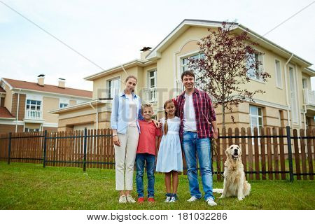Happy parents, children and their dog on green grass by new house