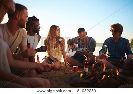 Group of friends listening to guy playing the guitar by campfire