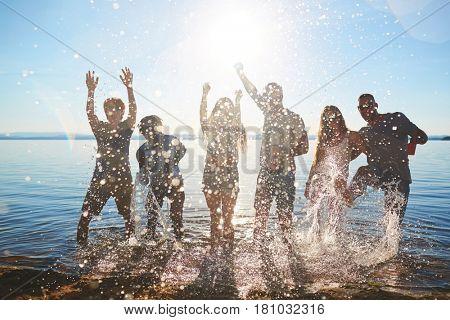 Happy buddies splashing water and raising hands