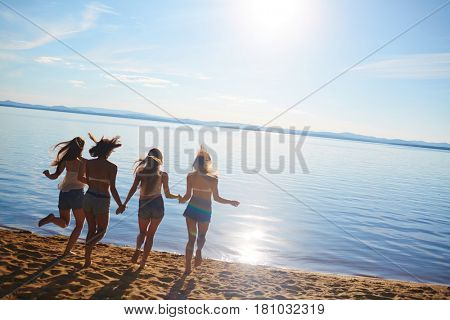 Four friendly girls running into water on summer weekend