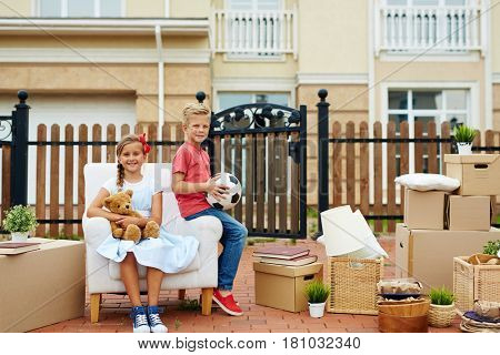 Youthful siglings sitting on armchair with packed things near by