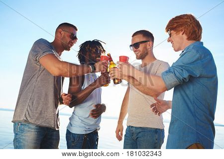 Happy guys toasting with drinks on the beach