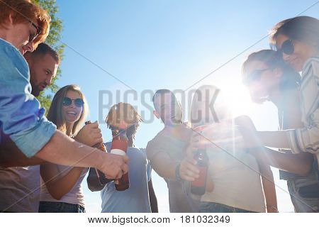 Young people toasting at beach party on sunny day
