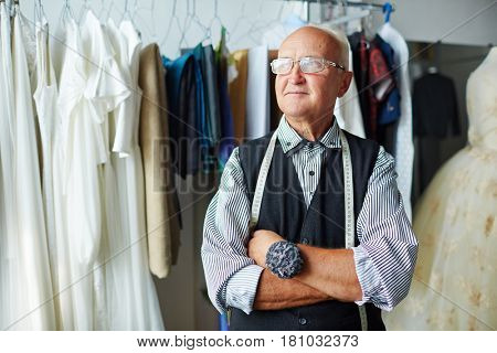 Senior tailor with measuring tape and needle-case