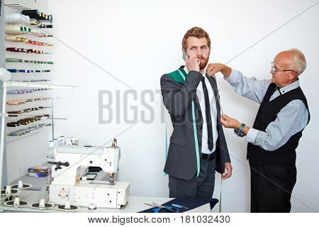 Young businessman speaking on cellphone while visiting tailor