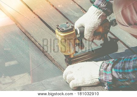 Carpenter Hand Or Hand Of Worker Drills A Hole With Wooden Plank Using Air Nailer Machine In Work Sh